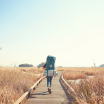 girl walking down path with backpack on her back