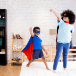 happy and confident young boy and girl playing superhero dress up