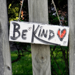 Be Kind sign with red heard hanging on fence